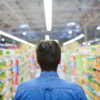Rear view of man walking along aisle of supermarket